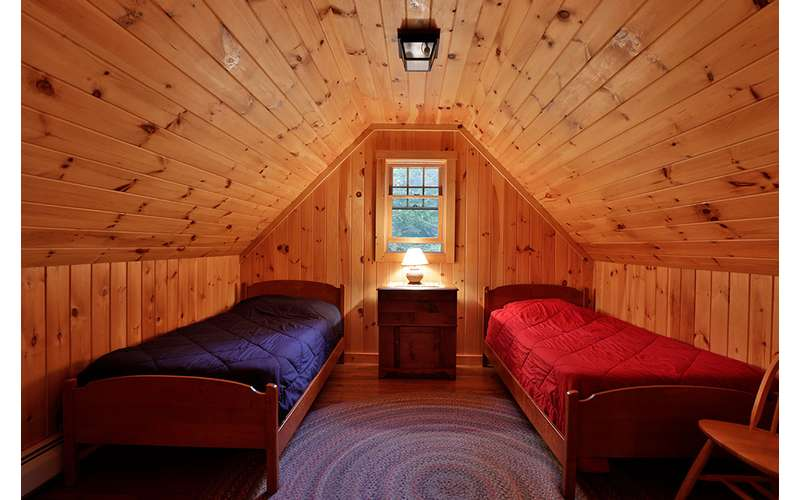 two twin beds each with a blue and a red comforter, wood paneling, low ceiling