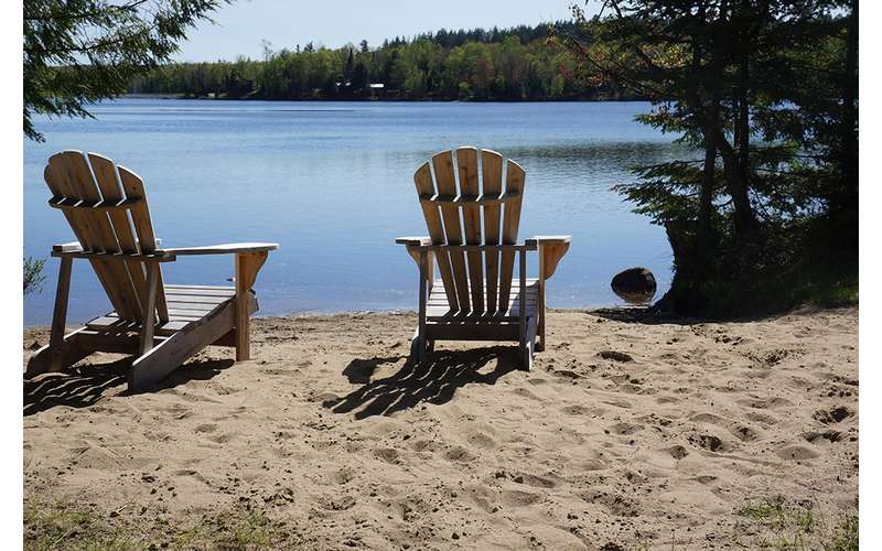 two Adirondack chairs on a beach facing the water