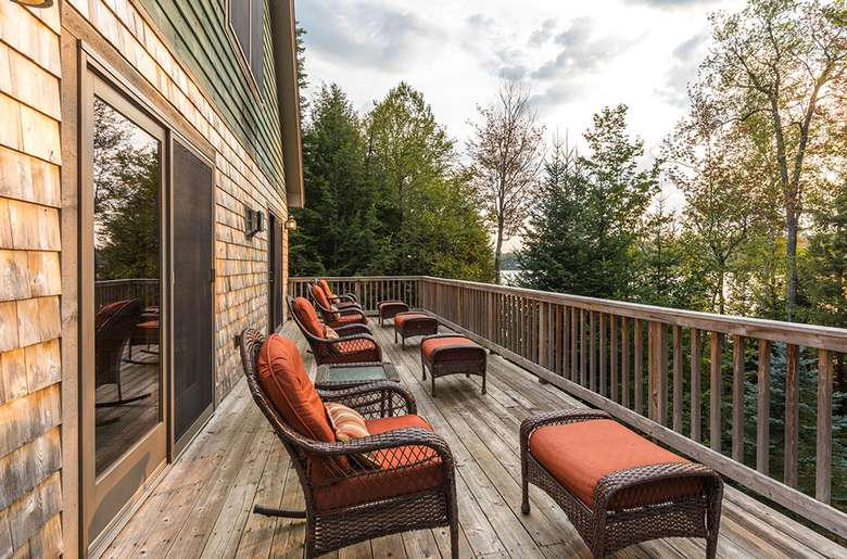 matching furniture on a large deck with views of woods and the lake
