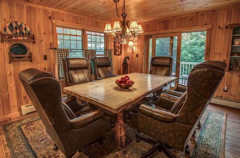 a dining room, wood paneling, large chairs, bowl of apples on the table