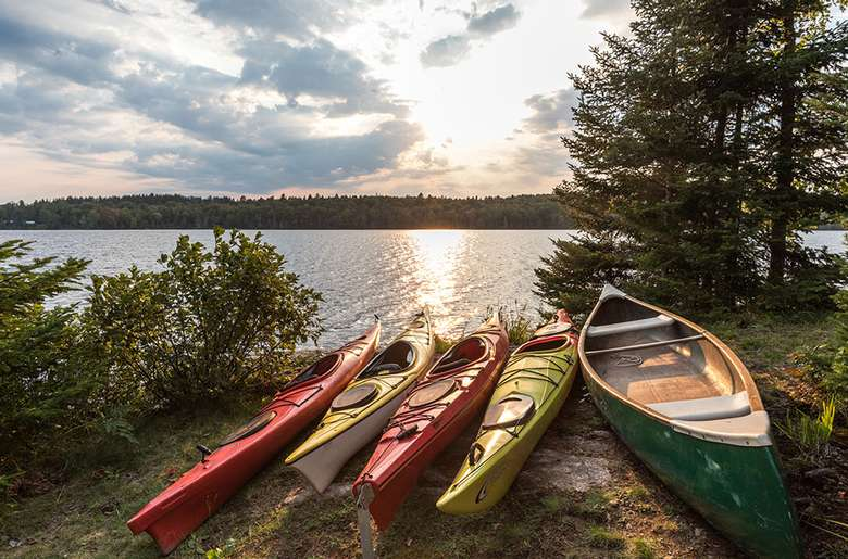 four kayaks and a canoe resting by a lake