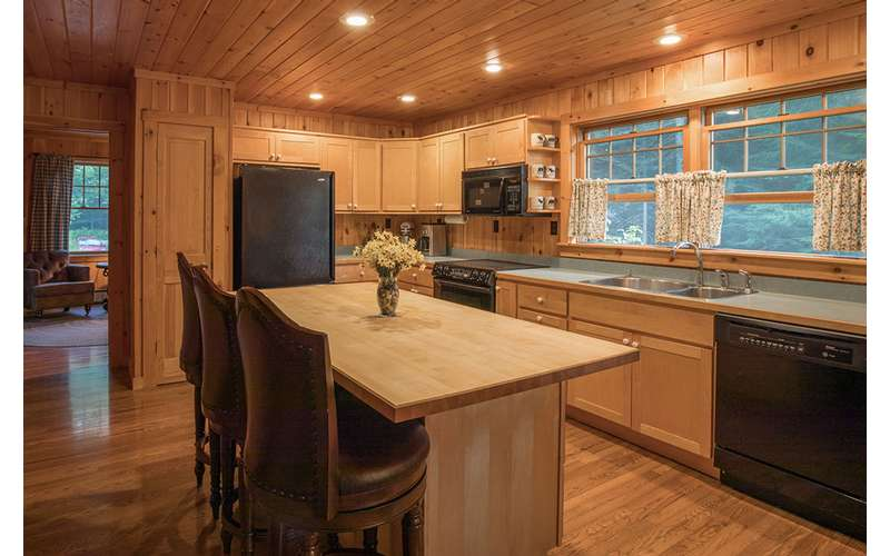 a kitchen with all wood paneling and cabinets, an island table in the middle
