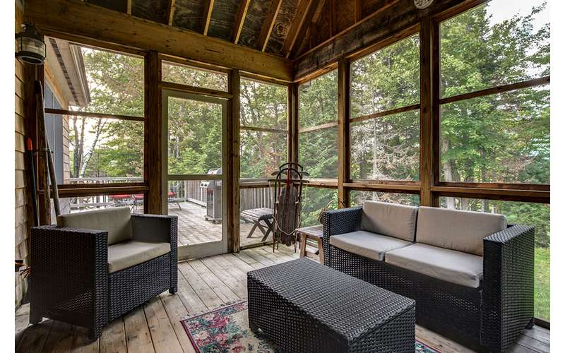 a closed in porch with floor to ceiling windows and elegant funiture