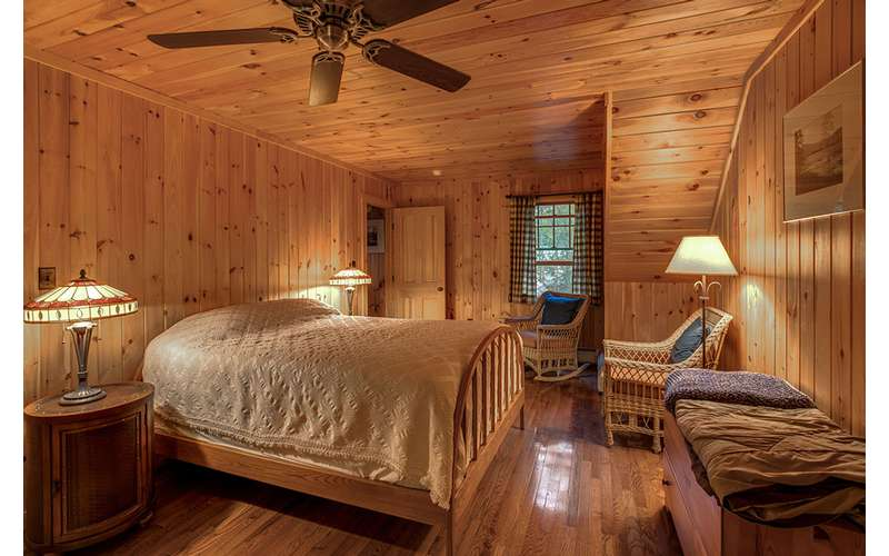 a furnished bedroom with wood paneling