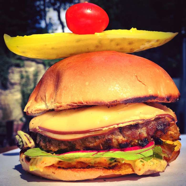 a burger with pickle and cherry tomato