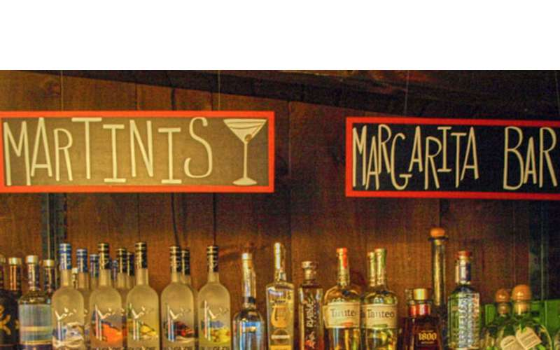 two signs for martinis and a margarita bar with bottles below