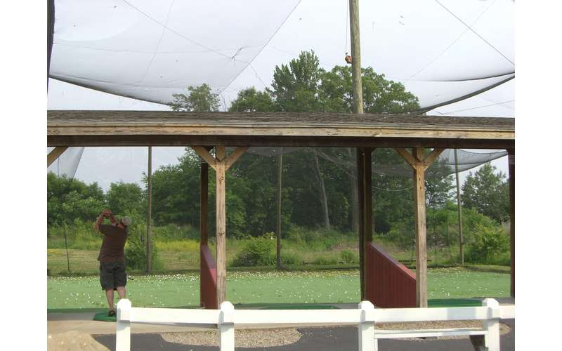 an enclosed golf driving range with netting