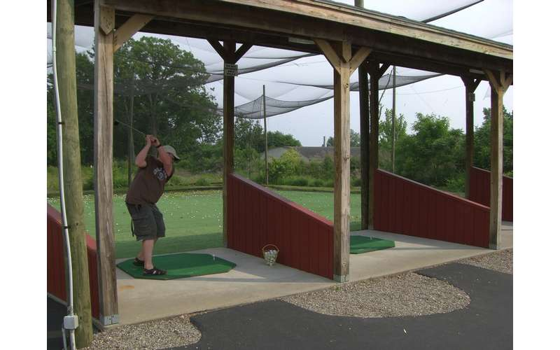 man at an enclosed driving range in the middle of swinging his golf club