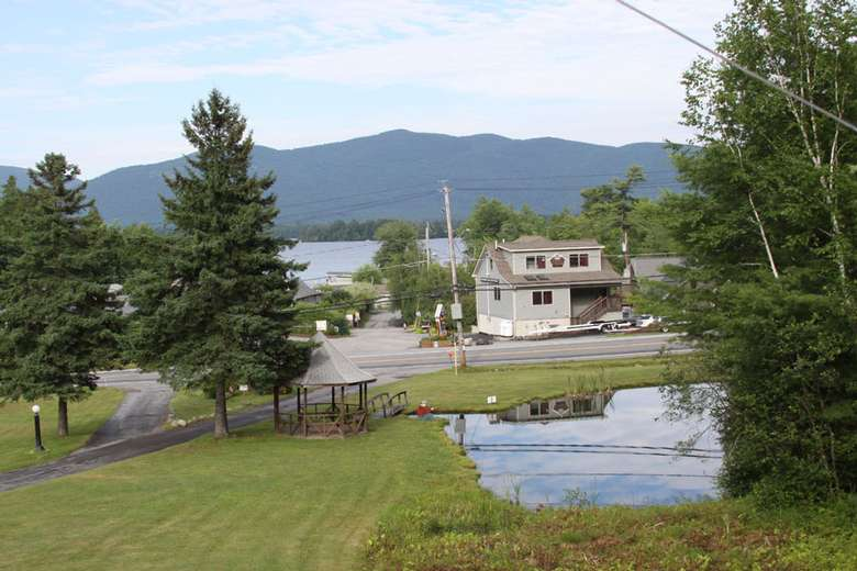 a large open property with views of a house and the lake and mountains