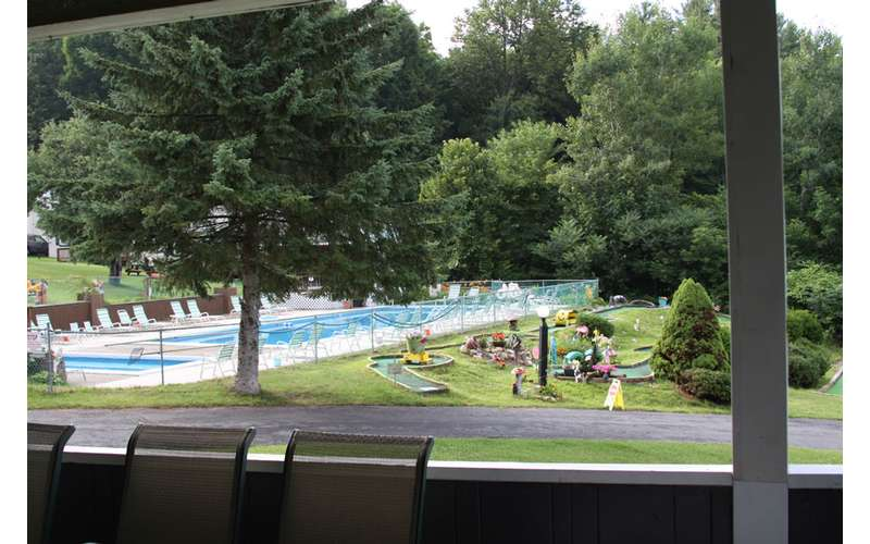 an outdoor pool in the background near trees and a kiddie pool
