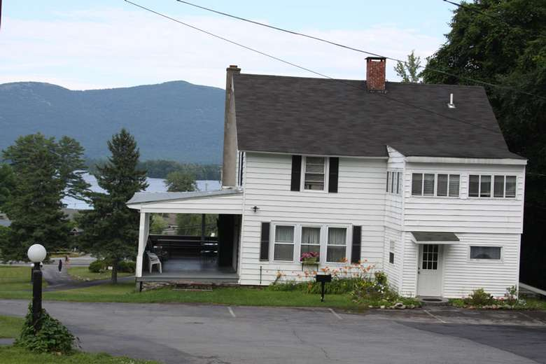 a large white house with a porch and chimney