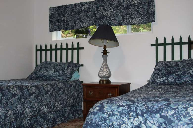 a bedroom with two beds that have matching blue blankets and pillows