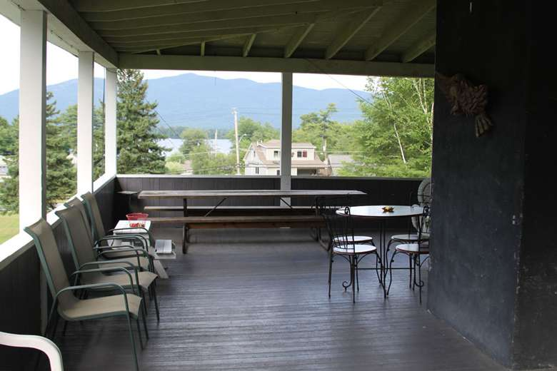 a spacious porch with chairs and tables