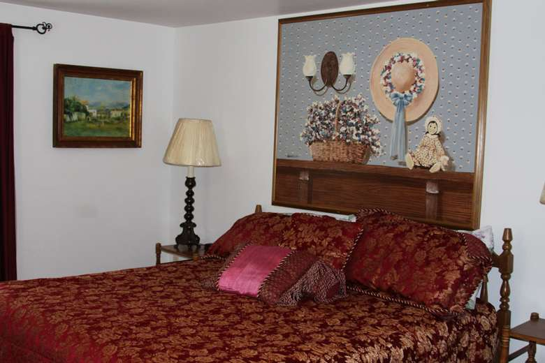 a bedroom with a bed that has red covers