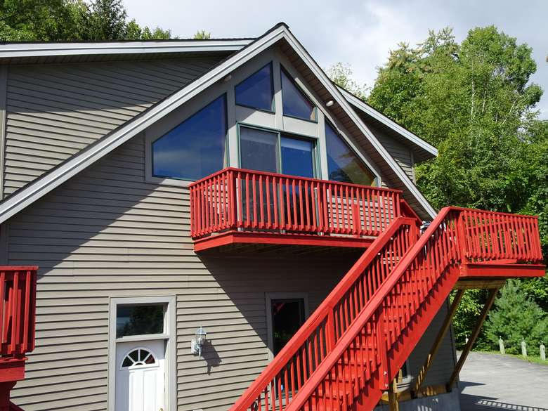 a large chalet with red stairs on one side of it outdoors
