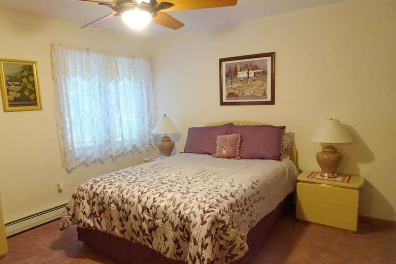 queen-sized bed with floral purple patterns
