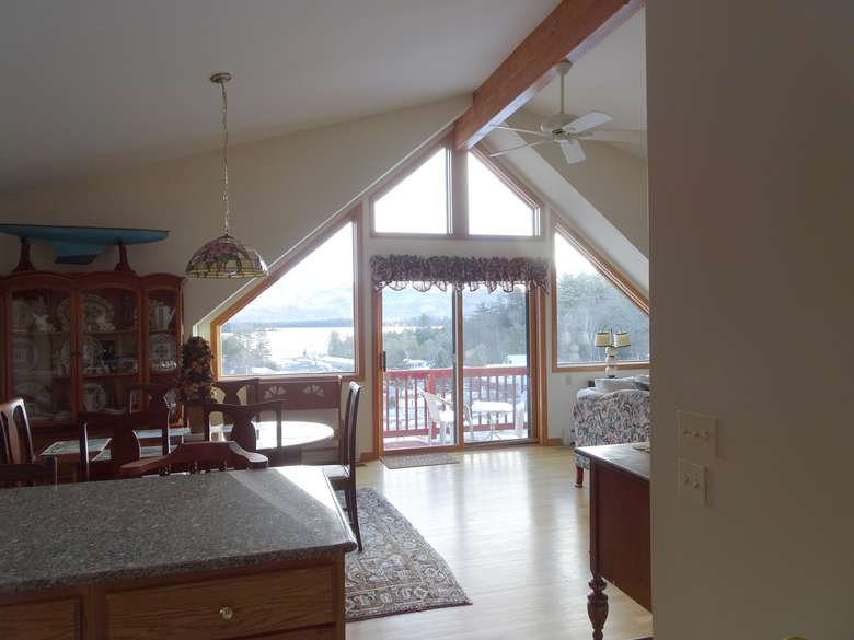 a room with views of the outdoors and the lake in the distance