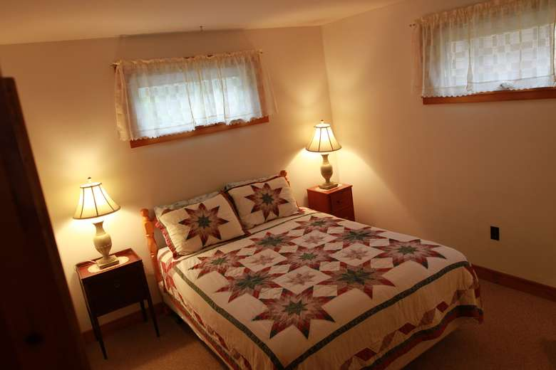 a bed with lamps on either side and a blanket with unique colored suns on them
