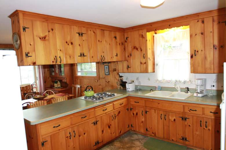 a kitchen area with wooden cabinets, a sink, and fridge
