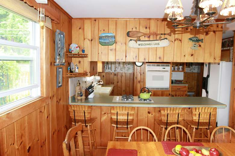 a rustic kitchen area with a counter and stools