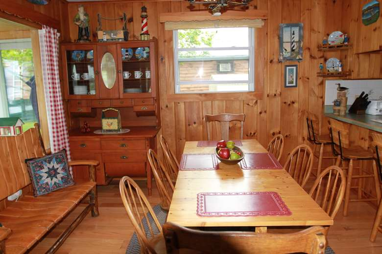 a wooden dining room table with a large decorated cabinet in the back