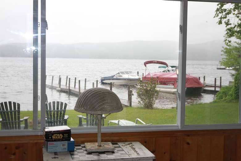 a view of the lake from a window inside a porch