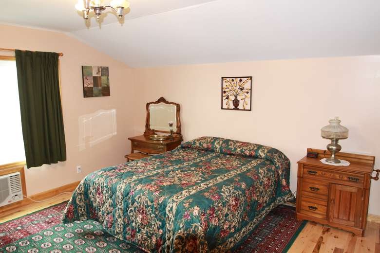 a large bedroom with a bed covered in a green blanket