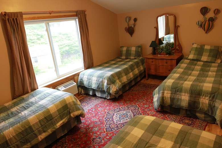 a bedroom with four twin-sized beds with plaid pattern blankets