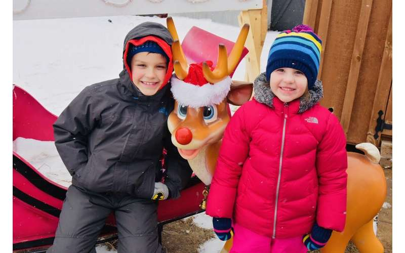 two kids with rudolph statue
