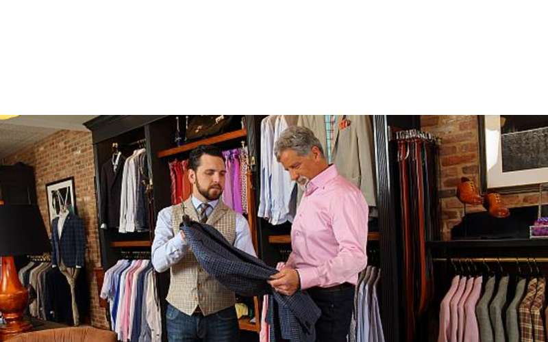 a man in a store showing another man a clothing item