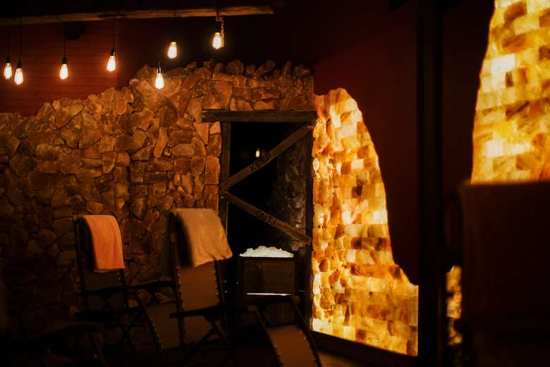 man-made salt cave with lounge chairs and salt blocks on the walls