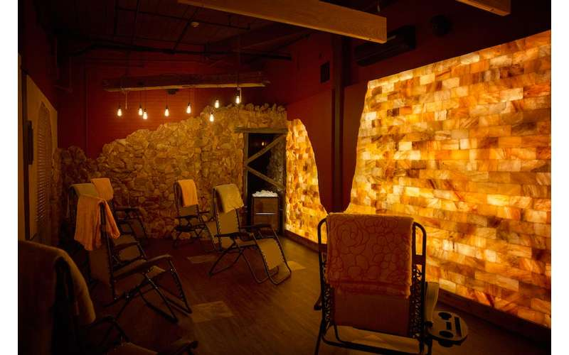 a man-made salt cave with lounge chairs and warm lighting