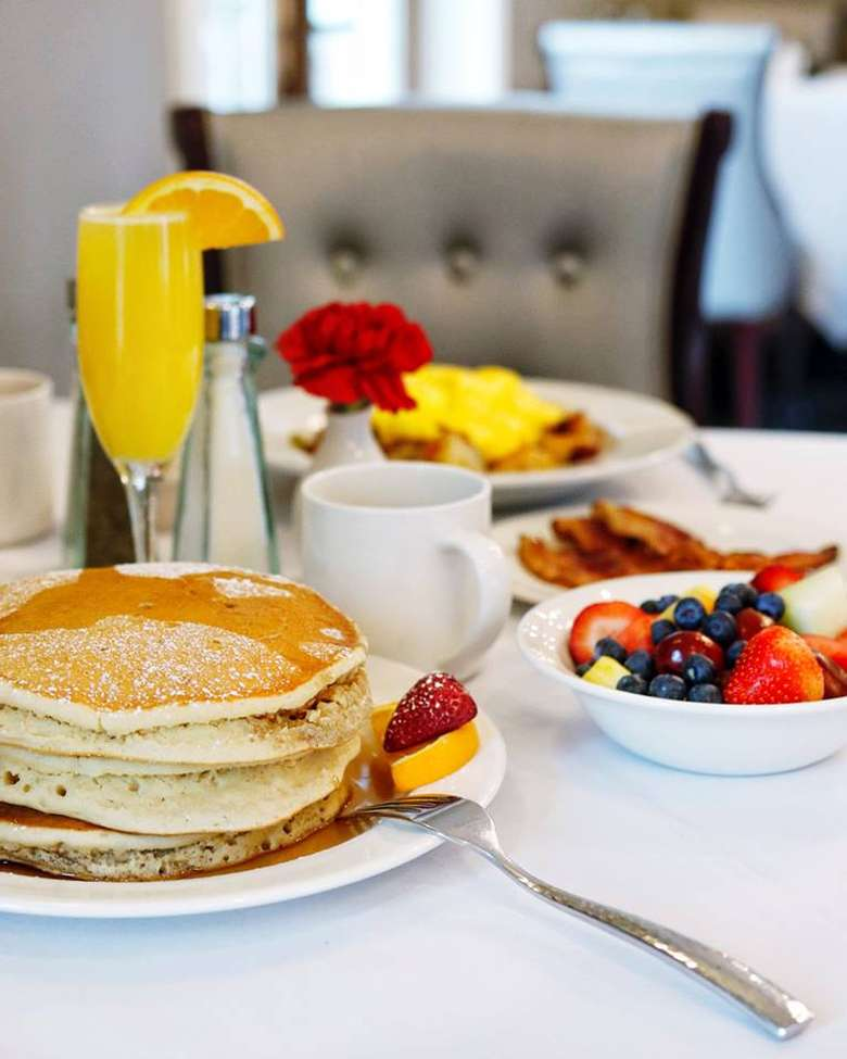 breakfast table with a stack of pancakes, a bowl of fruit, and a mimosa