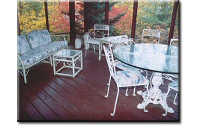 a porch with a glass round table and chairs