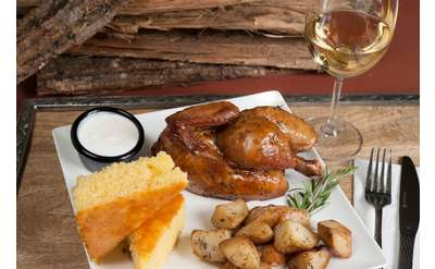 a whole chicken dinner with cornbread and potatoes