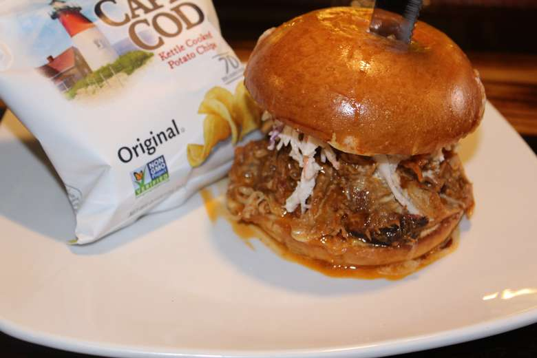 pulled pork sandwich on a bun with a side of cape cod chips