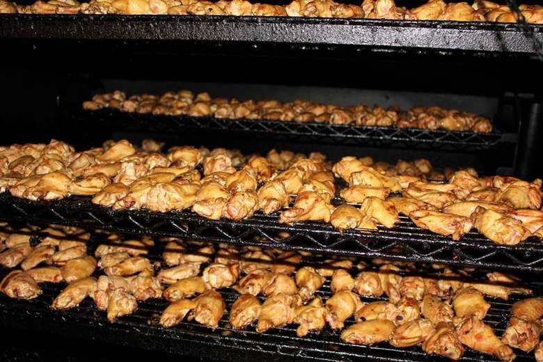 rows of chicken wings on rotisserie