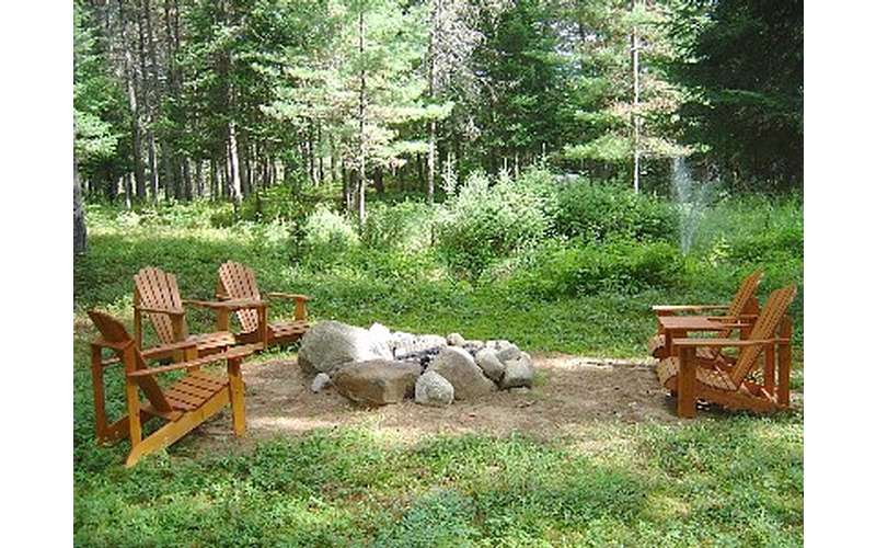 a campfire with Adirondack chairs around it