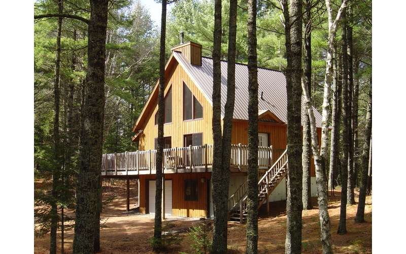 a two-story house surrounded by pine trees