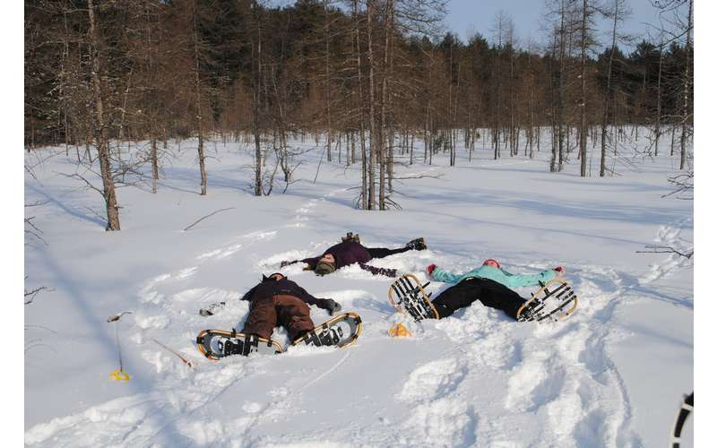 three people wearing snowshoes and laying on the snowy ground