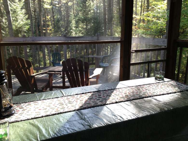 a screened porch with a picnic table
