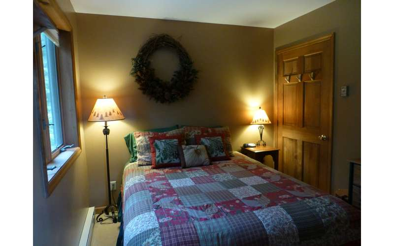 a bedroom with blankets and lamps that are Adirondack inspired