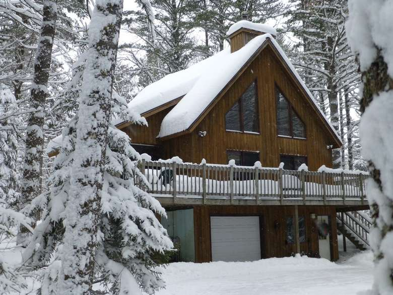 a two-story house in the woods covered in snow during winter