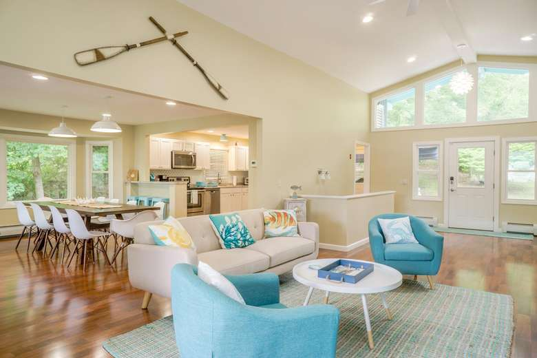 a living room with light blue and beige furniture, lacrosse sticks hanging on the wall