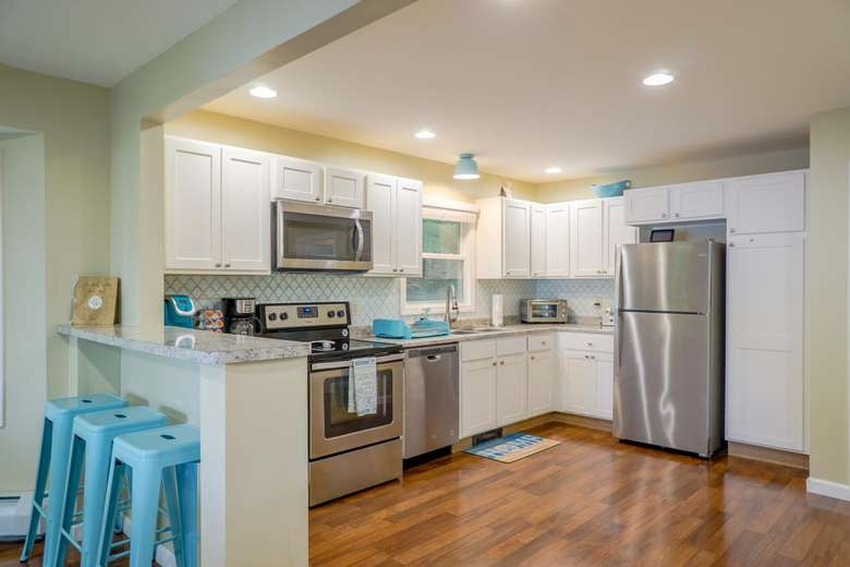 a kitchen with stainless steel appliances, blue stools at a bar, and hardwood floors