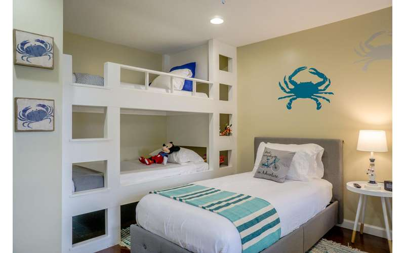 a bedroom with a twin bed bunk beds, and crab images on the walls