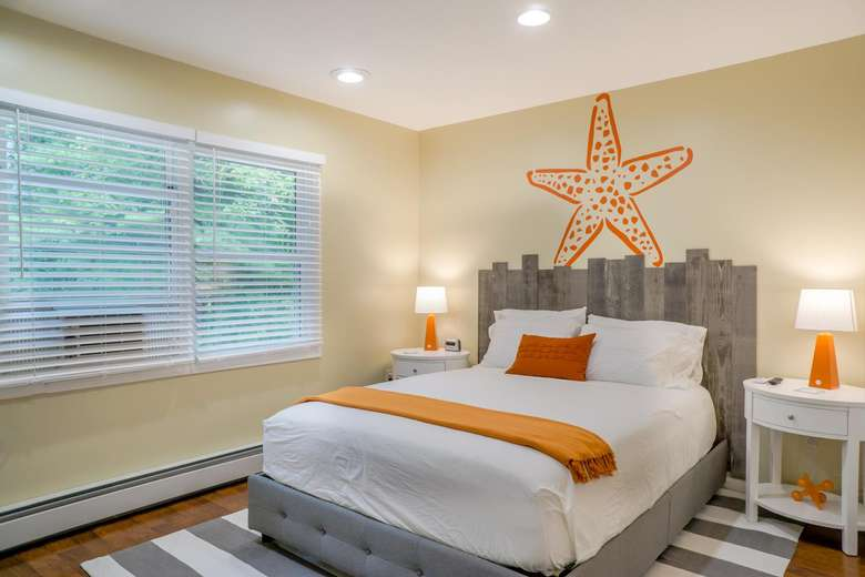 a bedroom decorated in burnt orange tones with an orange starfish above the bed