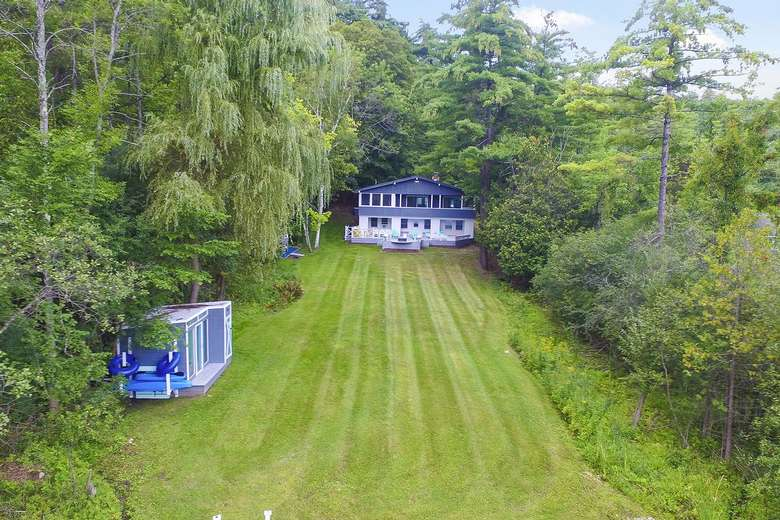 a somewhat aerial view of the house with a huge lawn and a beach house