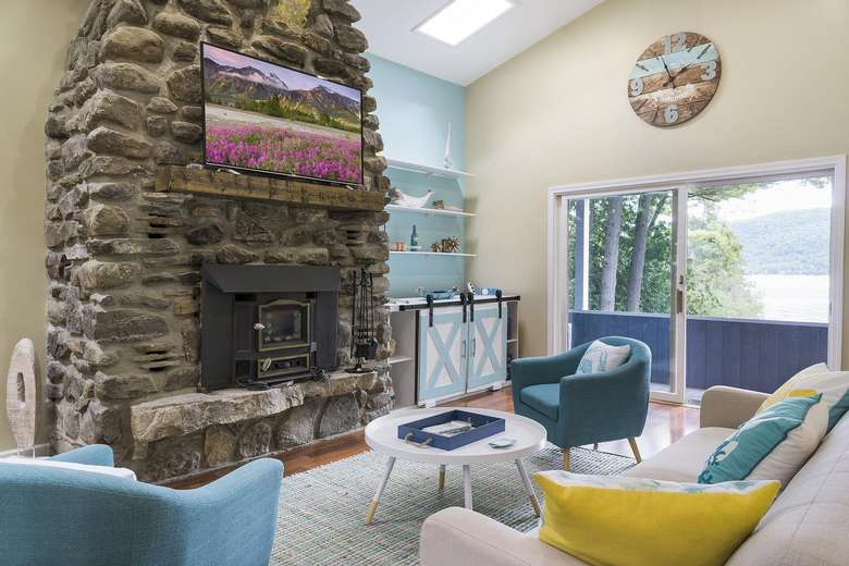 a large living room with colorful furniture and a large stone fireplace
