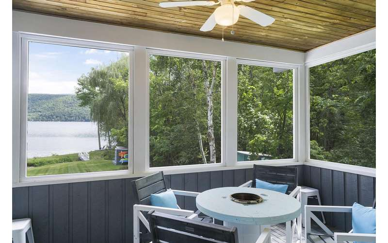 a screened in porch with a lake view